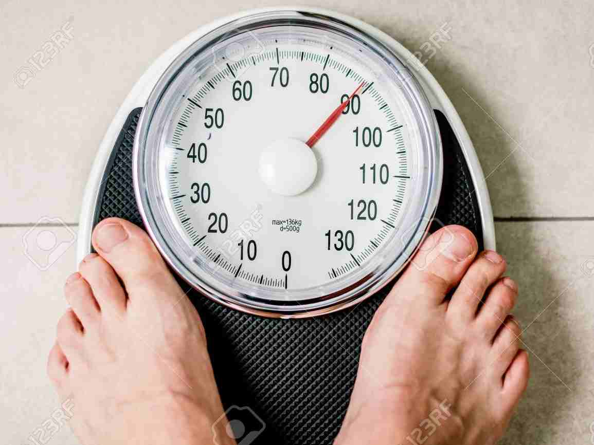 115162523-close-up-weighing-scale-man-standing-on-weigh-scales